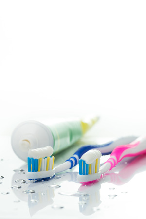 Toothbrushes and toothpaste tube on white background photo