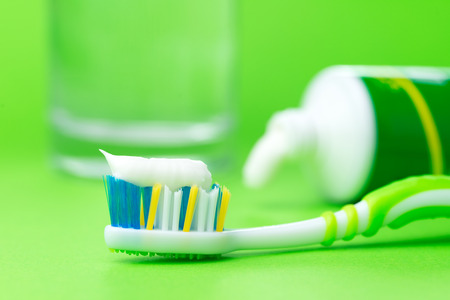 Close up of toothbrush and toothpaste tube on green background photo