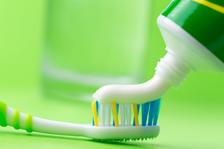 oral care: Close up of squeezing toothpaste on toothbrush on green background