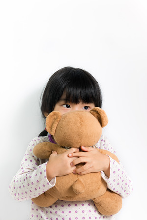 Little child in pyjamas holding teddy bear