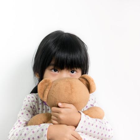 Little child in pyjamas holding teddy bear photo