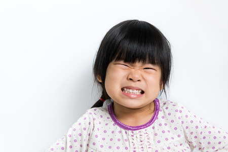 Little Asian girl wearing pyjamas doing silly face Stock Photo