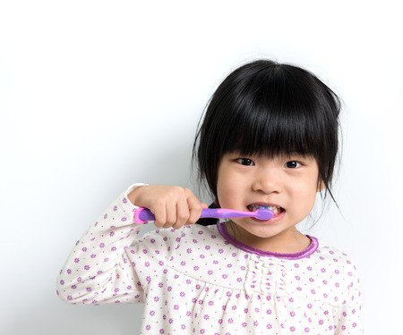 Little Asian girl in pyjamas brushing teeth