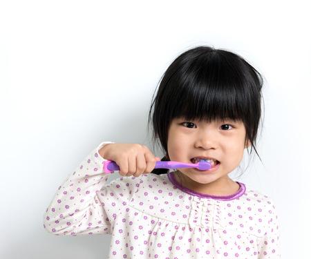 brushing: Little Asian girl in pyjamas brushing teeth