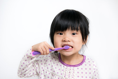 Little Asian girl in pyjamas brushing teeth