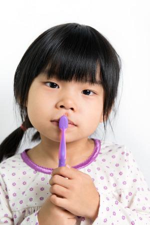 Little Asian girl in pyjamas holding toothbrush Stock Photo