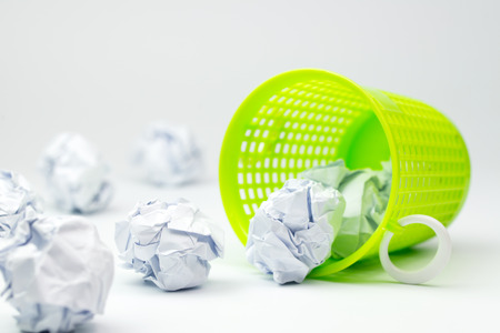 Green trash bin and crumpled paper balls on white background photo