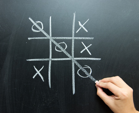 Hand drawn tic tac toe game on blackboard