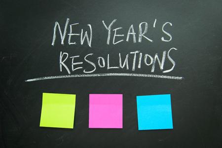 La resolución de la palabra de año nuevo escrito en la pizarra con las notas en blanco