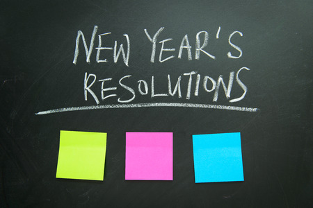 resolutions: The word New Years resolution written on the blackboard with blank notes