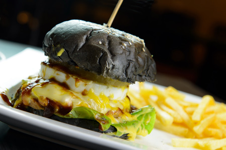 cheesy: Cheesy chicken burger with charcoal bun and served with french fries