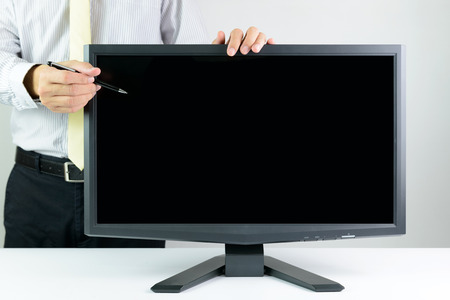 Businessman with pen pointing at blank monitor screen photo