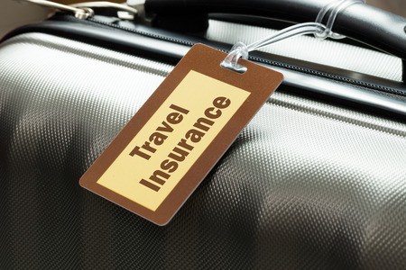 maleta: Seguro de viaje etiqueta de equipaje atado a una maleta Foto de archivo
