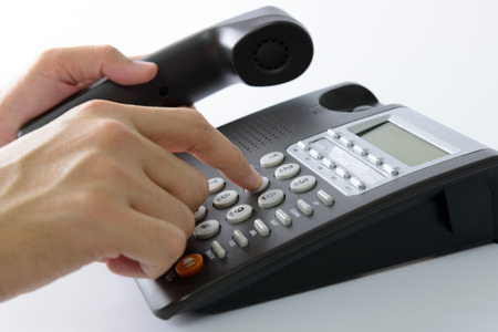 office phone: Close up of man dialing on a landline telephone