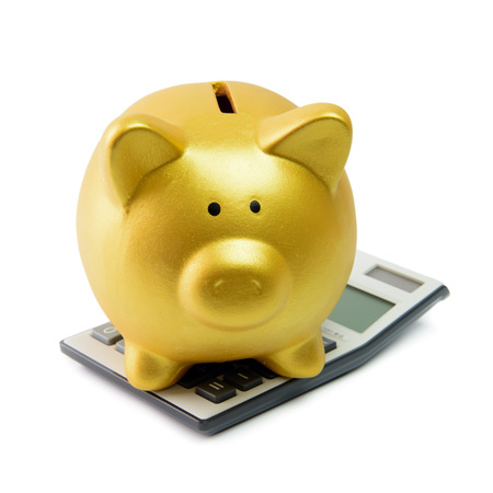 Calculating finance concept illustrated with piggy bank sitting on a calculator