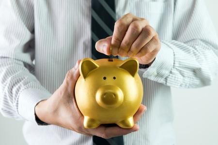 white piggy bank: Close up of businessman putting coin into golden piggy bank