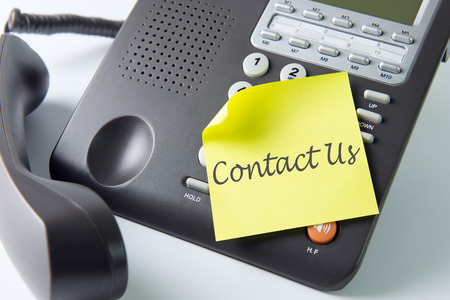 get help: Contact us on yellow sticky note on the telephone Stock Photo