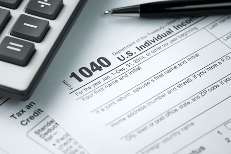 government services: Filling income tax form with pen and calculator