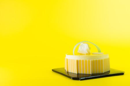 Mango mousse cake isolated on yellow background