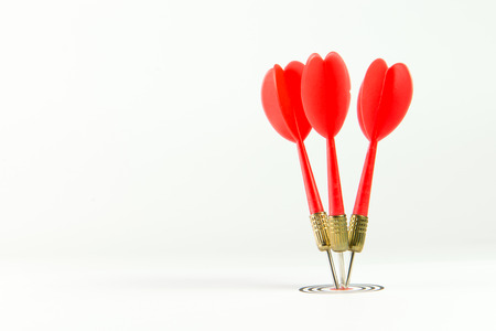 Three red darts pinned right on the center of dartboard Stock Photo