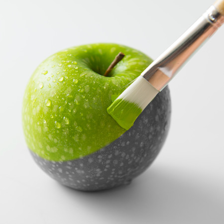 black color: Painting a fresh green apple with paintbrush Stock Photo