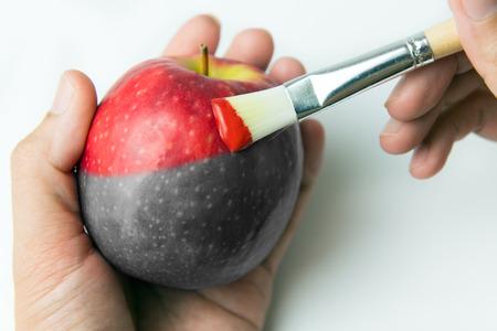 Pintura de una manzana roja fresca con la brocha Foto de archivo