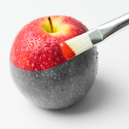 Painting a fresh red apple with paintbrush Stockfoto