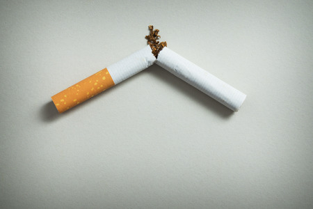 decease: Close up of broken cigarette on grey background Stock Photo