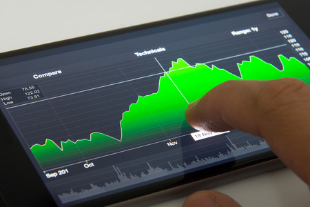online trading: Hand touching stock chart on mobile phone