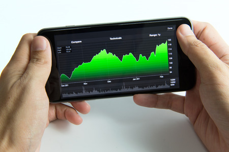 online trading: Man holding mobile phone with stock chart screen