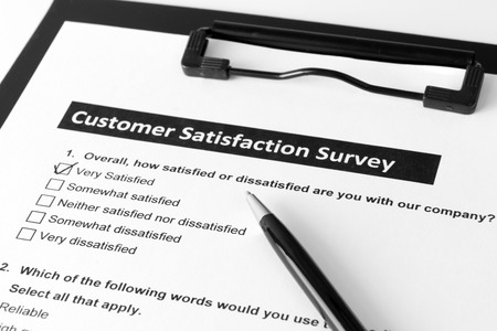 Filling customer satisfactory survey form with pen Stock Photo