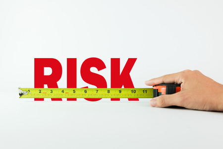 Measure the word Risk with measuring tape on white background