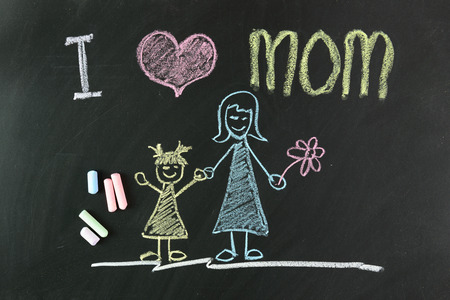mother days: Child drawing of I love mom picture using chalk on blackboard