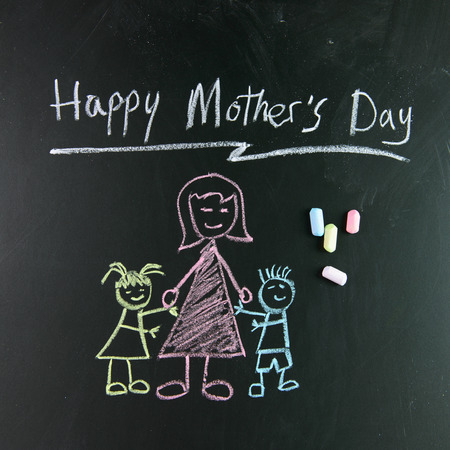 Child drawing of happy mothers day picture using chalk on blackboard