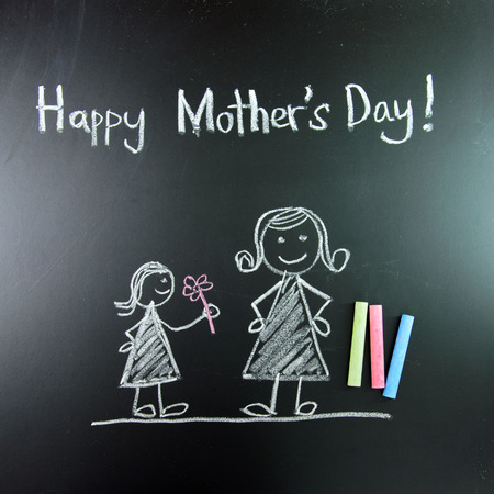Child drawing of happy mothers day picture using chalk on blackboard photo