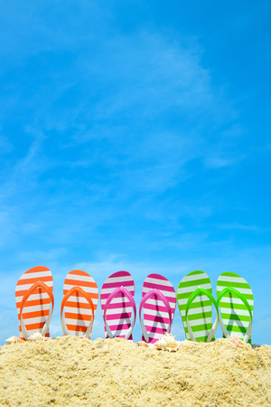 Fila de flip flops en playa multicolor contra el cielo azul