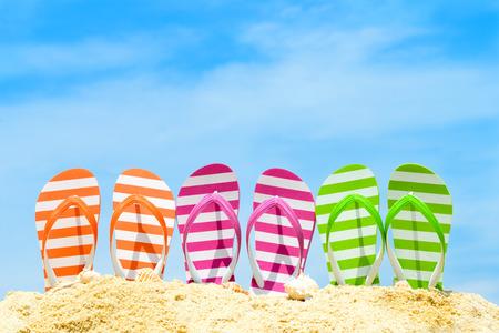 sandals: Row of multicolor flip flops on beach against blue sky