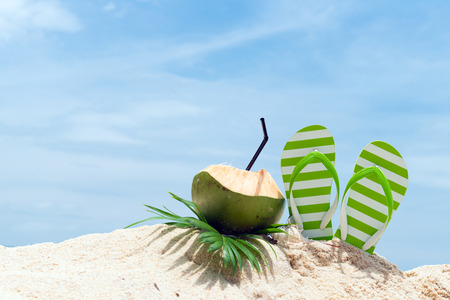 Pair of green striped sandal and coconut drink on the beach Stockfoto
