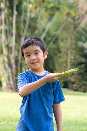 Little Asian boy playing Frisbee in the park