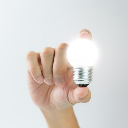 innovation: Hand holding a glowing light bulb over white background