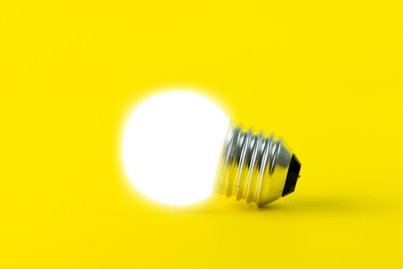 glowing light bulb: Glowing light bulb isolated on yellow background