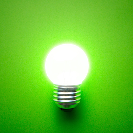 isolated on green: Glowing light bulb isolated on green background
