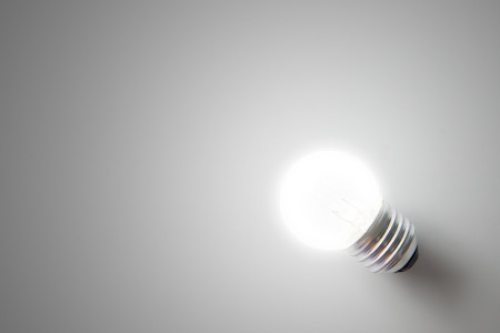 Bright clear electric light bulb isolated on grey background