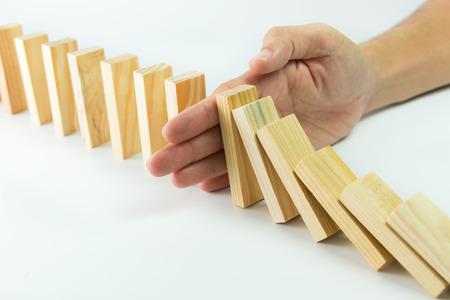Concepto de la solución con la mano deteniendo bloques de madera de caer en la línea de dominó Foto de archivo
