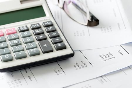 Cierre plano de la calculadora y las gafas en la declaración presupuesto financiero