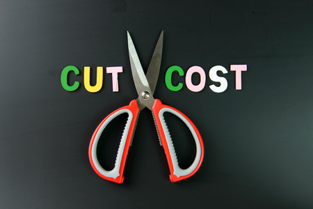 credit crisis: Cost cutting concept illustrated with pair of scissors between the words cut and cost on black background