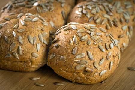 bollos: Close up of whole wheat buns with sunflower seeds on chopboard