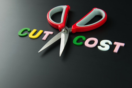 cutting costs: Cost cutting concept illustrated with pair of scissors between the words cut and cost on black background