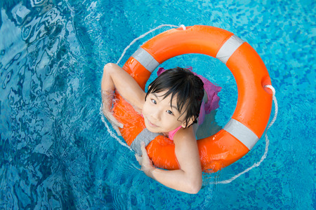 nadar: Pequeña muchacha asiática con el anillo de agua de naranja en la piscina