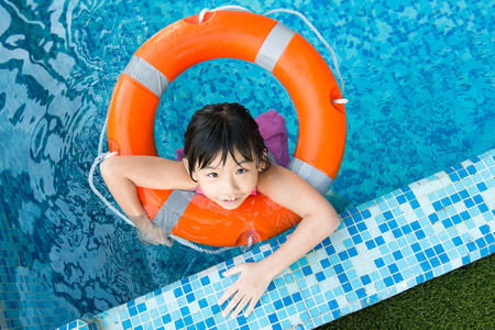 orange water: Little Asian girl with orange water ring in swimming pool